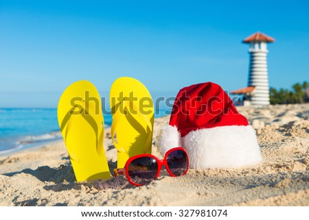New Year celebration at the seaside. Santa hat, sandals, sunglasses - christmas holiday at sea. - stock photo