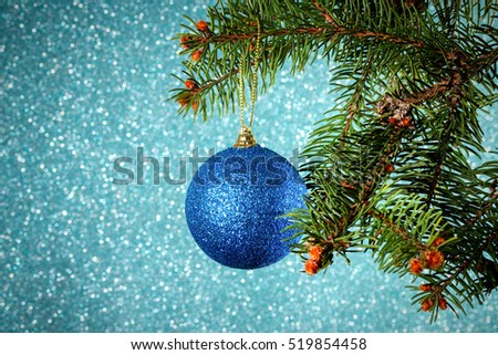 New Year. Christmas. Round blue Christmas toy hanging on the branches of a Christmas tree on brilliant background with bokeh, card