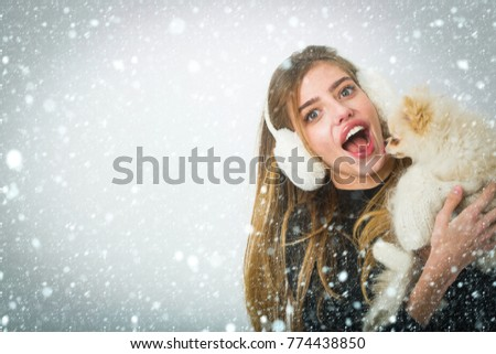 new year christmas snow concept Dog in hand of woman on white background. Xmas party and vacation. Woman with small dog of Pomeranian Spitz. Girl with happy face in gloves and ears. New year of dog