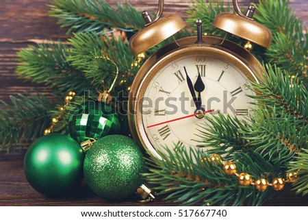 New Year clock and fir branches with Christmas balls.
