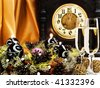 New Year composition with old clock, champagne and garland with candles - stock photo