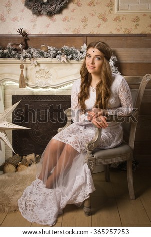 New Year Concept. Attractive woman posing by the fireplace