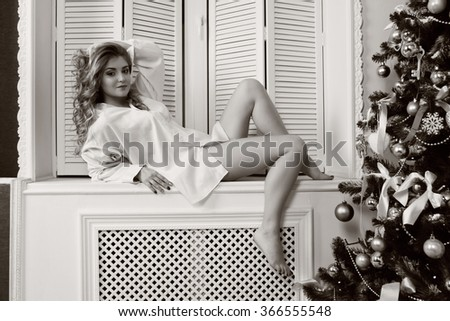 New Year concept. Beautiful girl sitting on windowsill in his underwear.