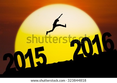 New Year concept: Silhouette of a man jumping from numbers 2015 to 2016 with sunrise background.  - stock photo