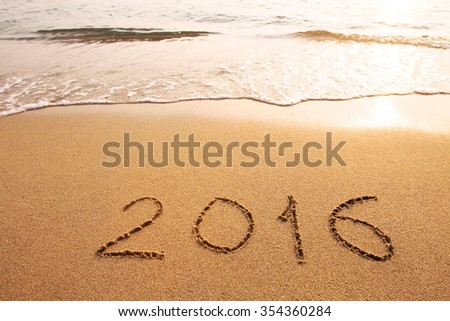 new year 2016 concept, text written on the sand of beach - stock photo