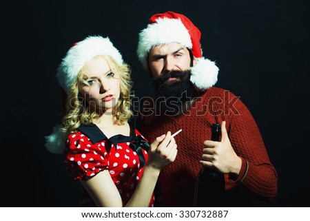 New year couple of blond woman with curly hair and man with long beard in red santa claus hat smoking cigarette holding wine bottle celebrating christmas standing on studio black background, vertical