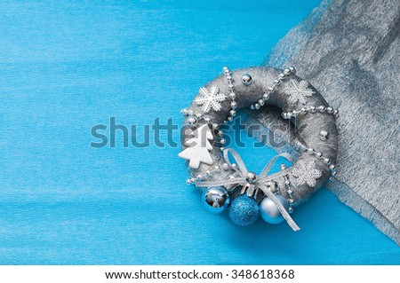 new year decoration wreath in silver style, Christmas on blue background with space for text - stock photo