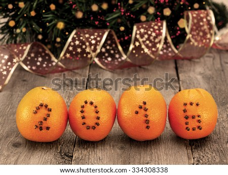 New Year  decorations with oranges and numbers of cloves on a wooden background - stock photo