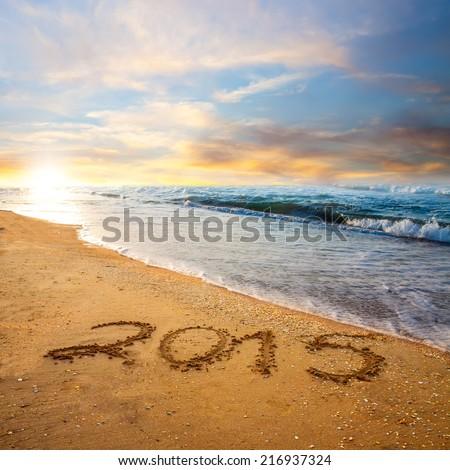 new year 2015 digits on ocean beach sand - stock photo