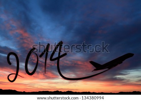 New year 2014 drawing by airplane on the air at sunset - stock photo