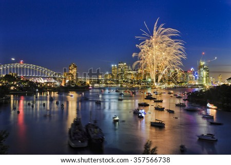 New Year eve fireworks in Sydney over Harbour towards CBD high-rises at sunset when sky is still blue and first light balls are bright - stock photo