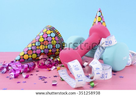 New Year Exercise Resolution with dumbbells and party decorations on white and blue background.  - stock photo
