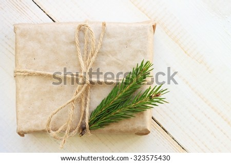 New year gift box handicraft wrapping, parchment twine fir tree twigs, cute simple last minute present handmade - stock photo