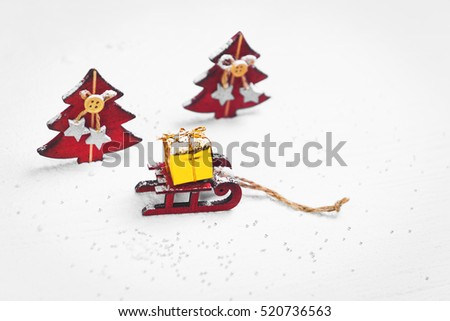 New Year gift card. Christmas toy landscape of snow, Christmas trees, wooden red sleigh (sled) with gold gift box. Place for text. Blank space.