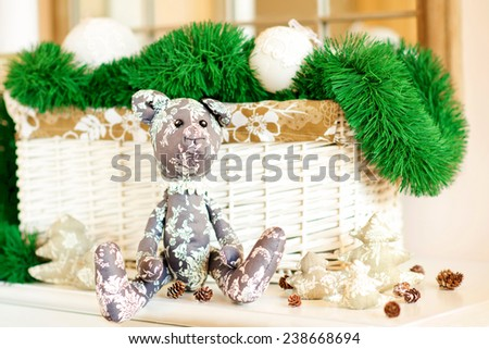 New year gift. Handmade tilda Teddy bear toy sitting on christmas background. Indoors still life. - stock photo