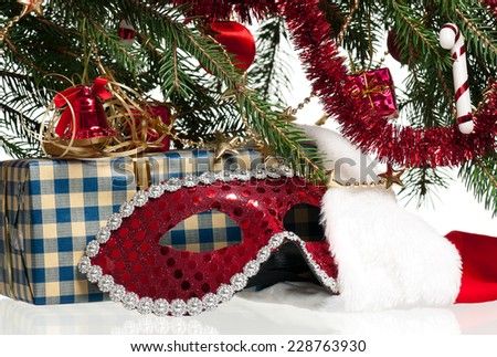 New year gift with carnival mask under christmas spruce over white background - stock photo