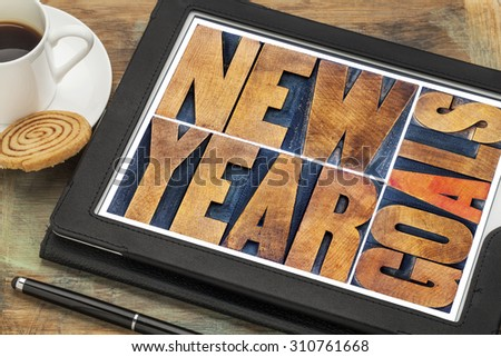New Year goals - word abstract in vintage letterpress wood type on a digital tablet with a cup of coffee - stock photo