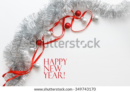 New year greeting card template made of red ribbon, silver tinsel and balls with copy space, horizontal view - stock photo