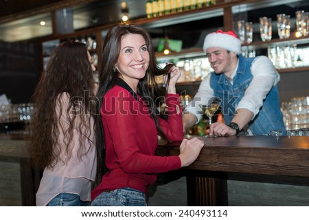 New Year in a bar. Young and beautiful girl is standing in a bar or pub and smiling. Bartender in Christmas hat is standing behind bar counter. Christmas is good with beer.