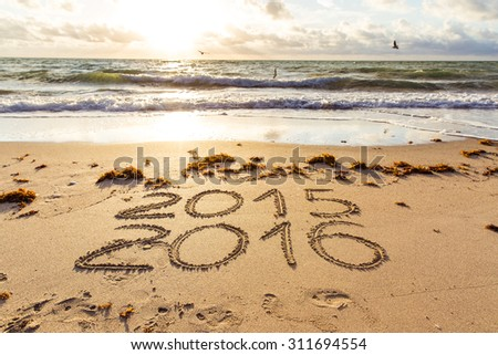 New Year 2016 is coming concept. 2015 and 2016 signs on a beach sand - stock photo