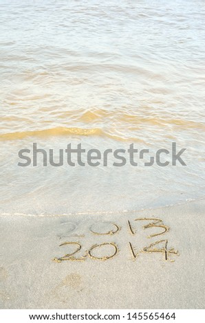 New Year 2014 is coming concept - inscription 2013 and 2014 on a beach sand - stock photo