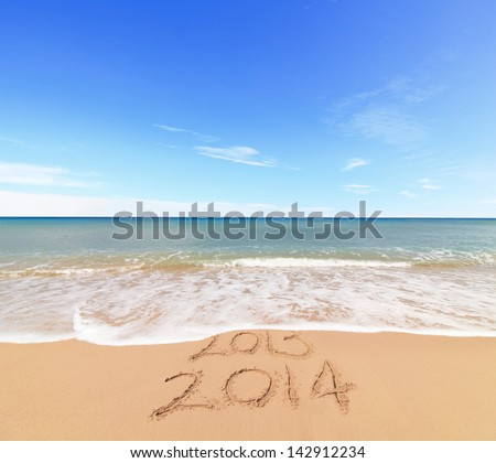 New Year 2014 is coming concept - inscription 203 and 2014 on a beach sand, the wave is covering digits 2013 - stock photo