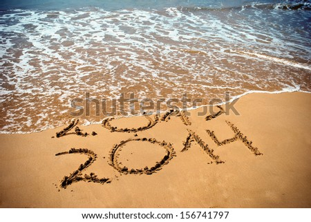 New Year 2014 is coming concept - inscription 2013 and 2014 on a beach sand, the wave is covering digits 2013