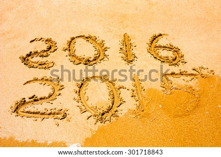 New Year 2016 is coming concept - inscription 2015 and 2016 on a beach sand, the wave is starting to cover the digits 2015
