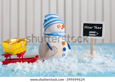 New Year is coming concept.  Snowman with red sled and gift or present stand near written on direction sign new year. - stock photo
