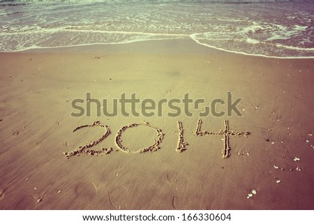 New Year 2014 is coming concept written on beach sand. vintage effect - stock photo