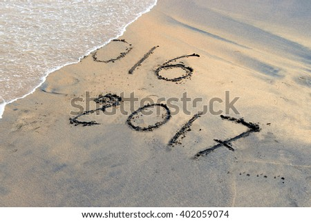 New Year 2017 is coming. New Year 2017 is coming concept - inscription 2016 and 2017 on a beach sand, the wave is covering digits 2016.