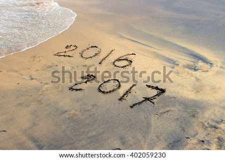 New Year 2017 is coming. Numbers 2017 and 2016 handwritten on seashore sand. Concept of upcoming new year and passing of time. - stock photo