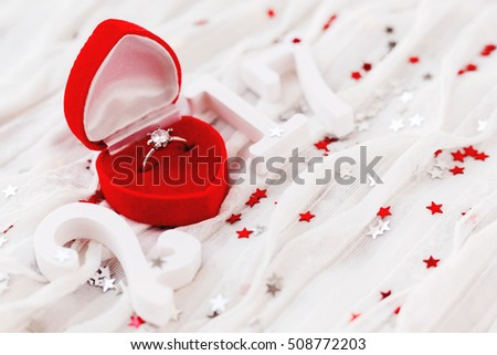 New Year 2017 on white fabric background with engagement diamond ring in red gift box. Good for Valentine's day and Happy New Year cards. Place for text.