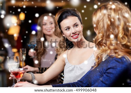 new year party, christmas, winter holidays and people concept - happy women drinking champagne and cocktails at night club over snow