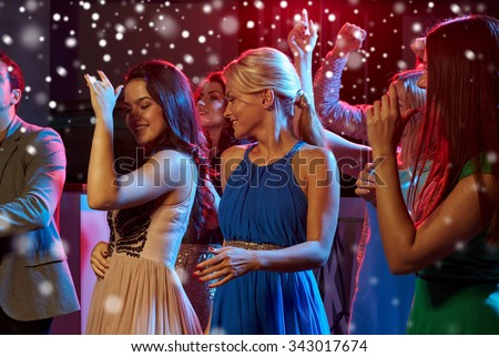new year party, holidays, celebration, nightlife and people concept - smiling friends dancing in club and snow effect - stock photo