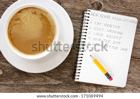 New year resolutions with  coffee cup on the wooden background - stock photo