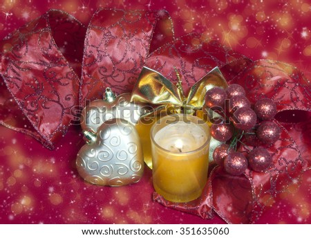New Year's composition on a red background - ball and ribbon and a candle - stock photo