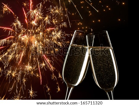 New Year's concept.   Celebration on New Year's Eve.    in the  background fireworks. Close up of two glasses of Champagne clinking together. - stock photo