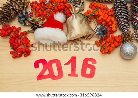 New Year's Eve 2016. Santa Claus hat, a bag with gifts, cones, rowan and toys. Christmas background - stock photo