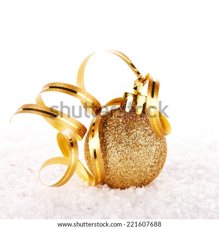 New Year's golden ball on snow with a tape. New Year's golden balls. Christmas balls. Christmas tree decorations. Christmas jewelry. - stock photo