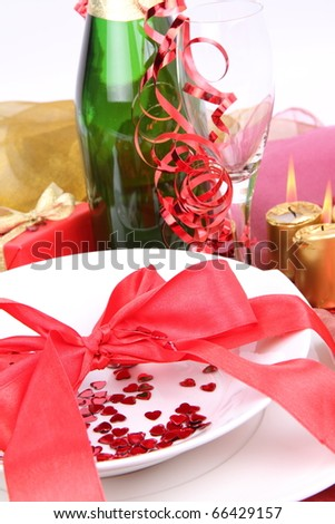 New Year's or Valentine's setting - a plate decorated with ribbon and heart shaped confetti, a bottle of champagne, a glass, candles, a gift in close up - stock photo