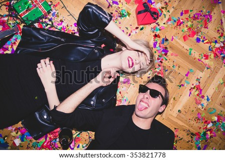 New Year's Party. Girl and boy laying on the floor full of confetti  - stock photo
