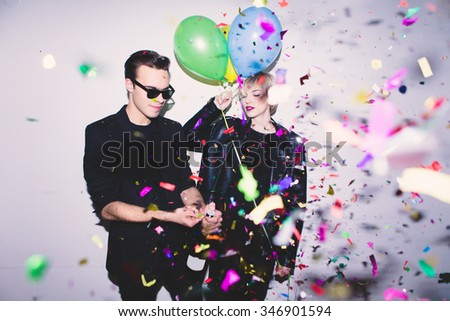 New Year's Party. Girl and boy posing in front of white wall with balloons  - stock photo