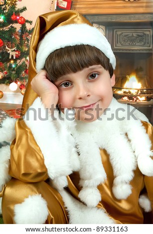 New Year's portrait of a boy in a golden suit against the fireplace and Christmas tree