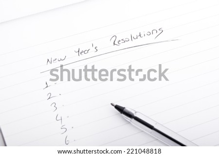 new year's resolutions on blank document - stock photo