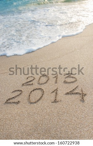 New Year 2014 season is coming concept - inscription 2013 and 2014 on a beach sand - stock photo