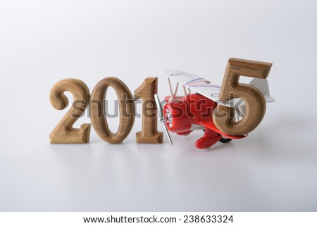 New year 2015 sign made by wooden number and red toy airplane - stock photo