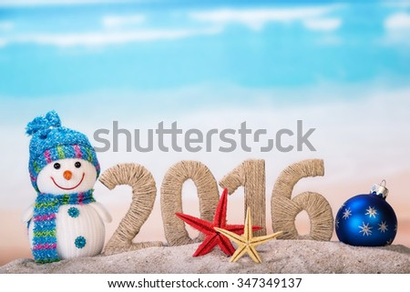 New year sign with starfishes on sandy beach and snowman
