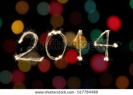 New year 2014 sparklers firework with colorful bokeh - stock photo
