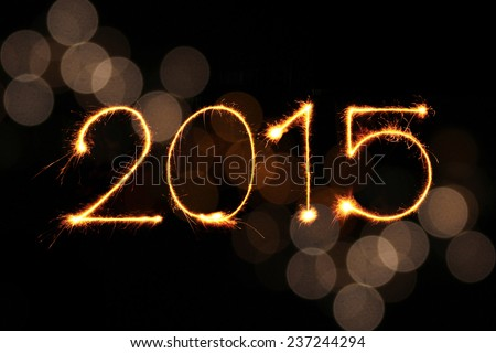 New year 2015 sparklers firework with defocused light blur bokeh background - stock photo